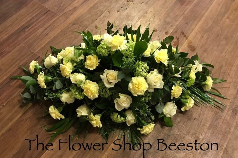 lemon and white carnation and rose casket spray the flower shop